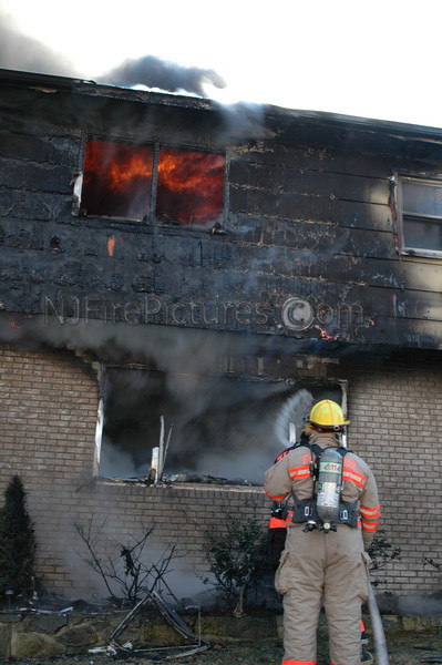 Fire fighters operating a handline. Heavy fire runs the second floor. Photo By: Adam Alberti