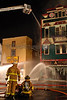 Firefighters operate hose streams in front of the fire building.