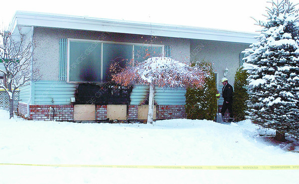 1914 Fraser House Fire/Friday Brent Braaten-Jan 8/2004  Prince George Fire Department personel and RCMP members enter a house Thursday morning to investigate a early morning fire. The female occupant of the house was taken to hospital.