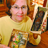 55 Year Easter Chocolate/Tuesday Brent Braaten-April 5/2004  Joyce Stunder holds a decorated Easter Cross made by 'Aunt Martha Chocolates' 'Prairie Maid Candies and a Chocolate Cupie made by Bond and Ronald. Both were given to her by her parents in the mid 1940's. She can actually rcall going into the candy store with her dad to buy the cupie. Her mother had stored the choolates in a cedar chest     befor giving them to Stunder. Her own daughter had kept her chocolate bunnies as well.