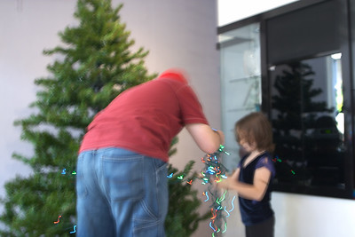 Dan and Natalia put the lights on the tree in preparation for the tree trimming party