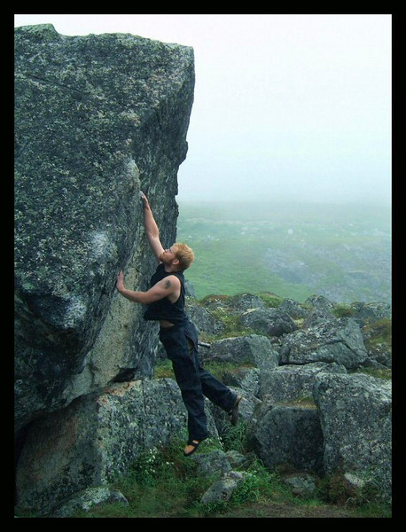With the rain moving in again, John Saari throws for a jug on a boulder in Archangel Valley.
