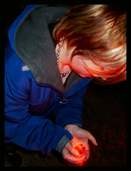 Alli warms her hands with a piece of the fire during a game of hot coal.
