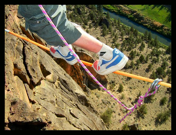 Many slackers prefer skate shoes over any other for slacking.  Larry Harpe shows his off high over the Crooked River at the Monkey Face Highline, Smith Rock, Oregon.