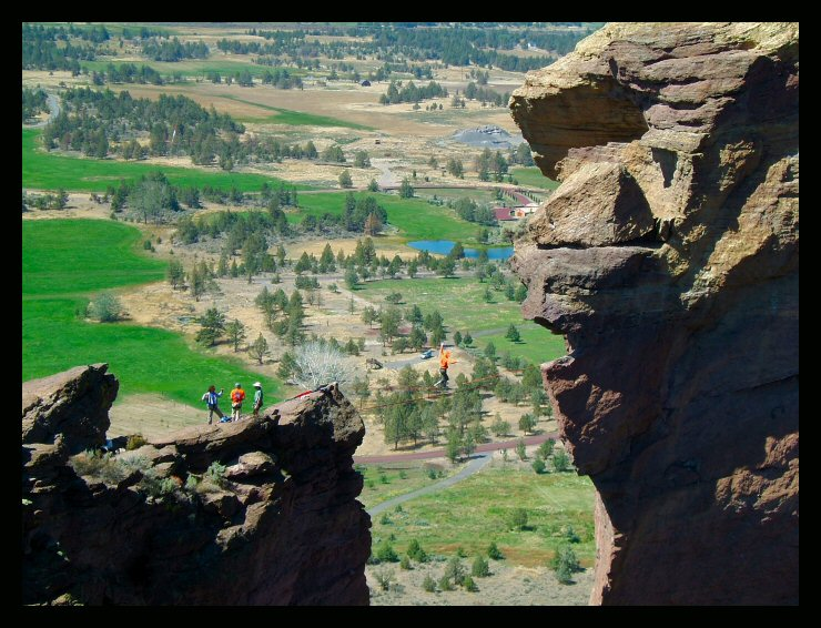 The Monkey looks down on Larry Harpe as he crosses the void into the mouth.  Monkey Face Highline, Smith Rock, Oregon.