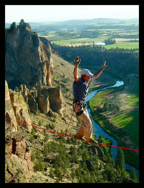 Arms up for balance, Shawn Snyder moves out across the void on the longer line at the Monkey Face, Smith Rock, Oregon.