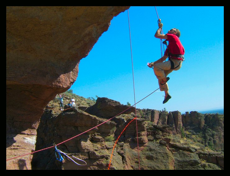 Larry Harpe moves onto the highline while Shawn Snyder swings out over the void during setup of the longer line at the Monkey Face, Smith Rock, Oregon.