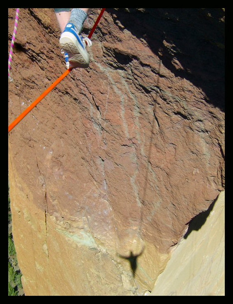 Shoes and a shadow belonging to Larry Harpe on the Monkey Face Highline, Smith Rock, Oregon.