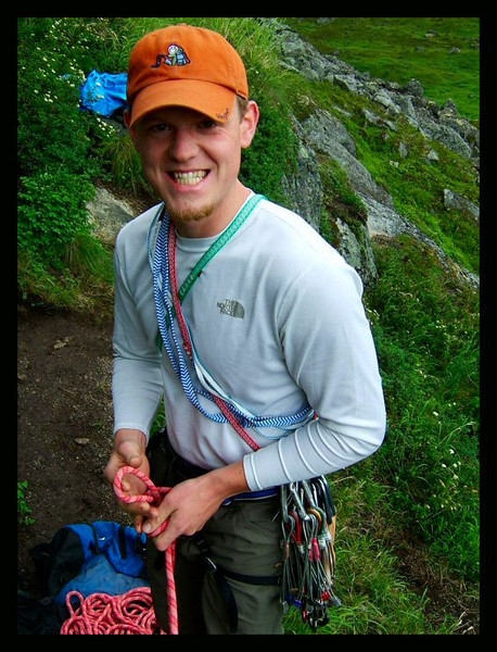 Chad Gailey gives off a grin, perhaps inappropriate to the situation as he is roping up to climb <i>Physical Attraction 5.8</i> in one of Archangel Valley's typical drenching downpours.