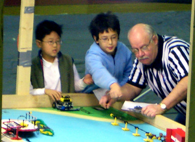 Two members of David's team, with their robot, and the ref.