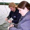 Ashley unhooks her fish
