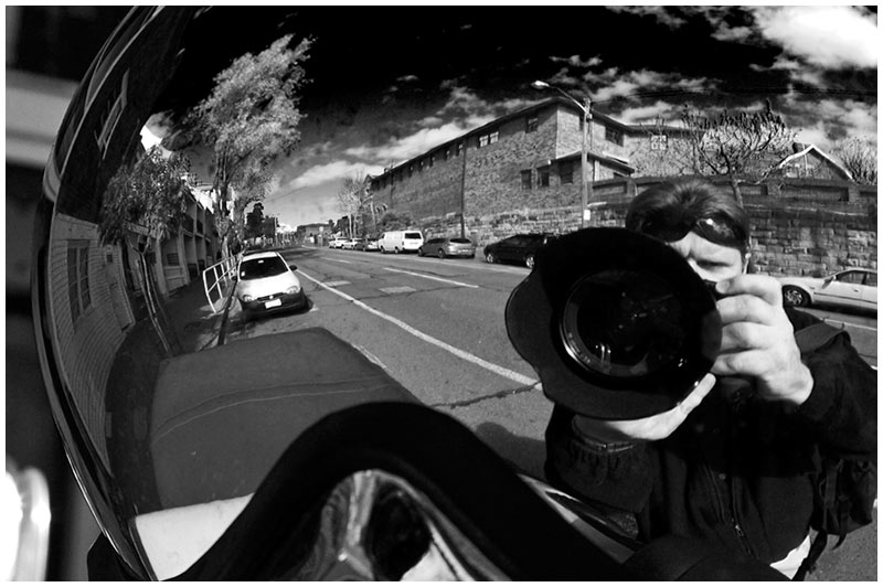 Bourke Street, Darlinghurst, Friday August 5th 2005. <br /> <br /> A self portrait of sorts. This photo is taken looking into the rear of a car roof mounted spotlight; the chrome surface acting as a mirror. <br /> <br /> EXIF DATA <br /> Canon 1D Mk II. EF 24-70 f/2.8L USM @40mm. 1/80s f/14. Aperture Priority. ISO 200.