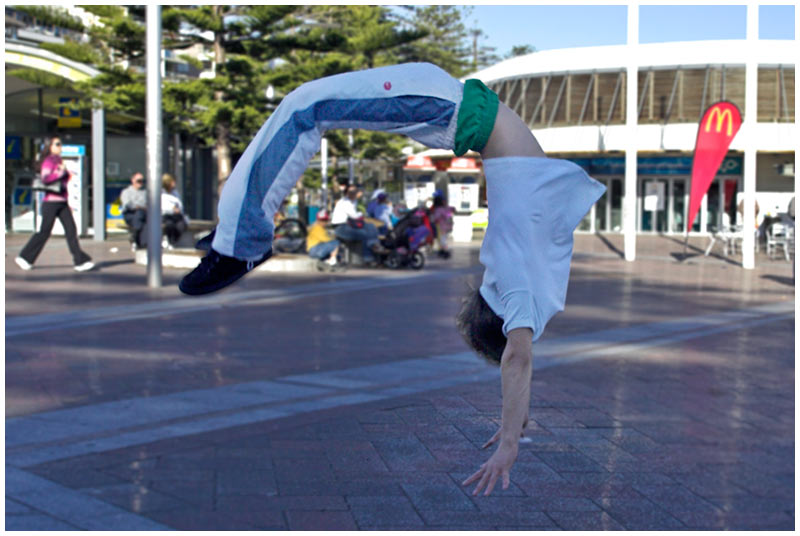 Manly Wharf, Manly, Sunday August 7th 2005. <br /> <br /> There are a number of kids who hang around the wharf at weekends and skateboard or perform incredible gymnastic feats. Lucas is one of them and here is in the middle of a triple backward somersault. <br /> <br /> EXIF DATA <br /> Canon 1D Mk II. EF 17-35 f/2.8L USM @35mm. 1/400s f/5.6. Shutter Priority. ISO 400.