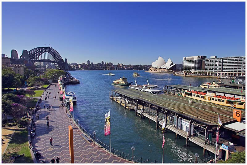 "Circular Quay, Sydney Harbour, Friday, July 29th 2005. <br /> <br /> A straight postcard style view of the harbour with the ferry terminals to the right. It's days like this, when the weather is perfect, that you look out across the harbour and just think ""wow""!  It's one of those ""life's good"" moments. <br /> <br /> EXIF DATA <br /> Canon 1D Mk II. EF 17-35 f/2.8L USM @17mm. 1/125s f/10. Shutter Priority. ISO 200."