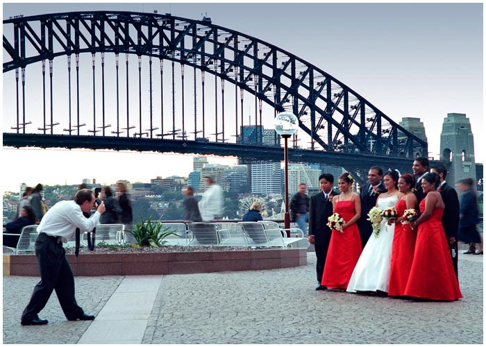May 8th 2005.<br /> <br /> Circular Quay.<br /> <br /> It was cool and dull, but that didn't deter this wedding party from posing for photographs at the foot of the Opera House. It's a very popular spot for wedding photography.<br /> <br /> EXIF DATA<br /> Canon 1D Mk II. EF 17-35 f/2.8L USM @35mm. 1/30s f/11. Shutter priority. ISO 400.