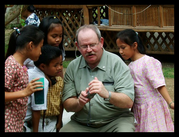 Ever popular with the little ones, Pat shows off his own photography for an eager crowd of admirers at Amparo Village, Philippines.