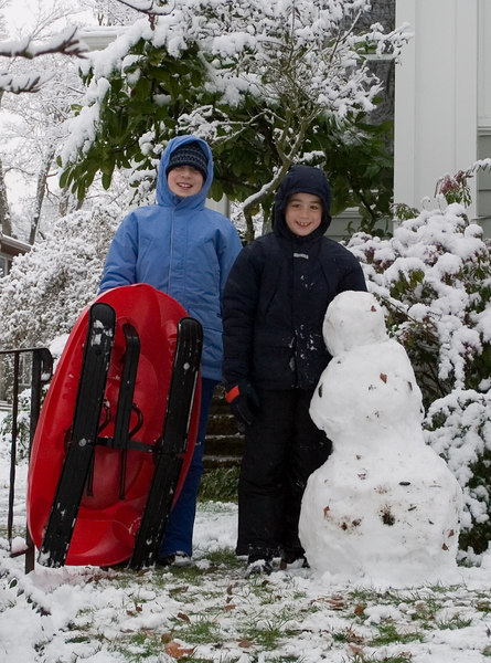Isabel and Benjamin with sleds and their snowman.