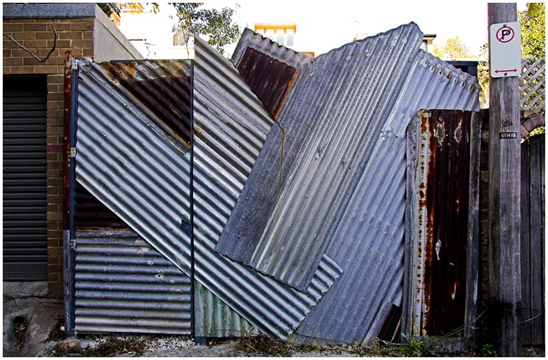 A back lane in Surry Hills, Saturday September 17th 2005. <br /> <br /> A rear gate constructed from old corrugated roof panels seems to be a worthy recycling effort. <br /> <br /> EXIF DATA <br /> Canon 1D Mk II. EF 17-35 f/2.8L@17mm 1/50s f/9 ISO 250.