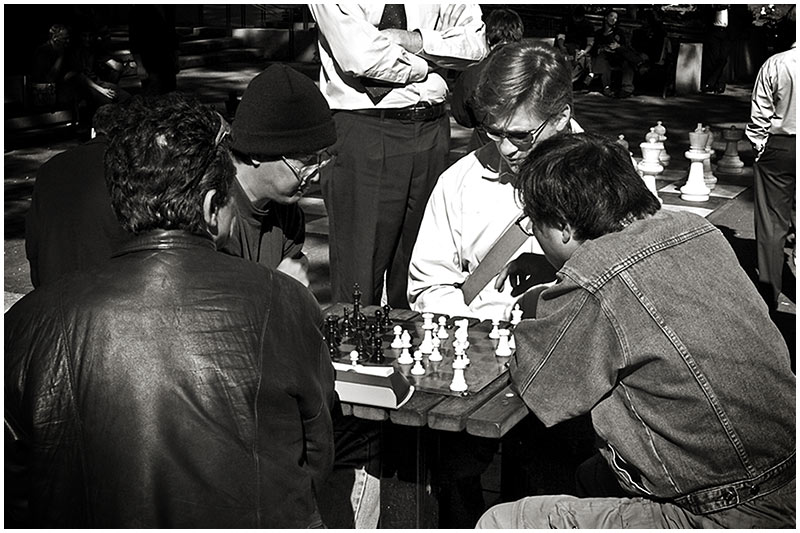 """Hyde Park, Thursday September 22nd 2005.   Chess matches are a popular lunchtime pursuit in this section of the park. Note the giant size playable chess set in the background which was the subject of <em><a href=""""http://sydneywebcam.smugmug.com/gallery/699850/2/32375687/Large""""target=""""_blank"""">a previous post.</a></em>  EXIF DATA  Canon 1D Mk II. EF 17-35 f/2.8L@35mm 1/100s f/14 ISO 200."""