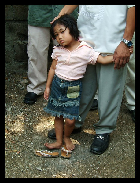 A young girl eyes the camera curiously from the shelter of her father's hand in Amparo, Philippines.