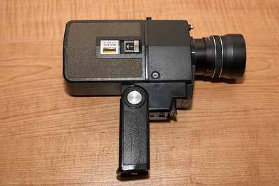 Pistol grip handle extended. Not sure what the small jack to the right of the film compartment is for, nor the silver button at the top left corner of the front of the camera, next to the lens