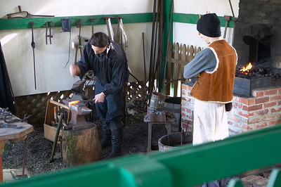 The blacksmith practicing his craft, while his apprentice looks on