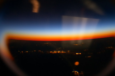 The concave windows in airplane doors do strange and beautiful things to sunsets