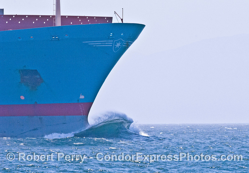 "A nice wave forms across the bulbous bow ot the commercial container ship ""Knud Maersk."""