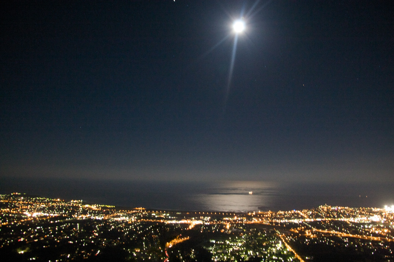 Wollongong under the moon • A view over Wollongong, south of Sydney, under a full moon.  Look at how the moon is so bright and the air so clear that we can see the very bright reflection of the moon in surface of the sea.