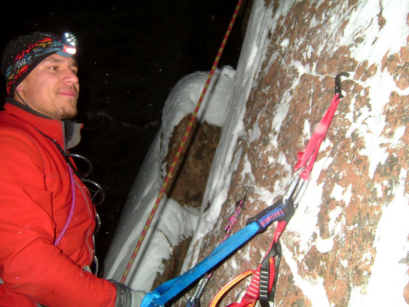 Kelsey's smile belies the screaming fear in his gut, hanging from a single icy hook on Chugach choss.