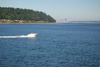 A boat speeding along past the ferry, and the Seattle skyline visible just around the point.