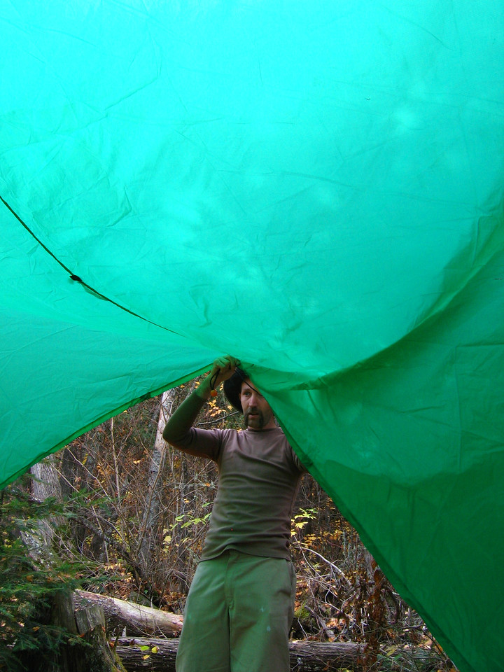 Tom helps put up a tarp to reserve the site.