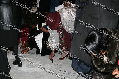 Members sign the floor of the Mount Carmel Church at the cornerstone dedication