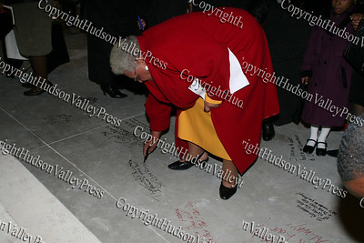 Roxy Royal signs the floor of the Mount Carmel Church at the cornerstone dedication