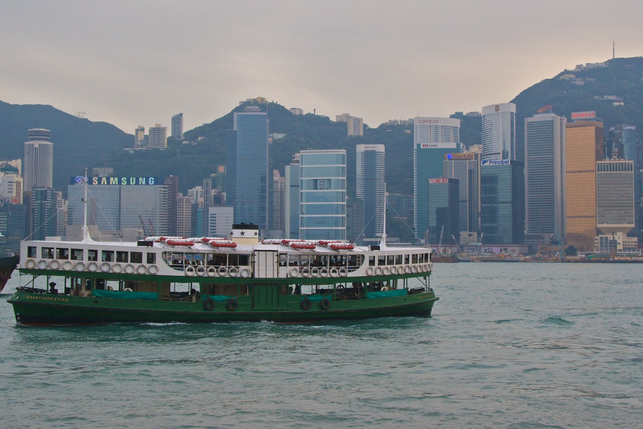 Star Ferry • A boat from the Star Ferry service, which shuttles between the Hong Kong island and Kowloon peninsula crosses Hong Kong Harbour. The waterfrong buildings of Hong Kong loom in the background.