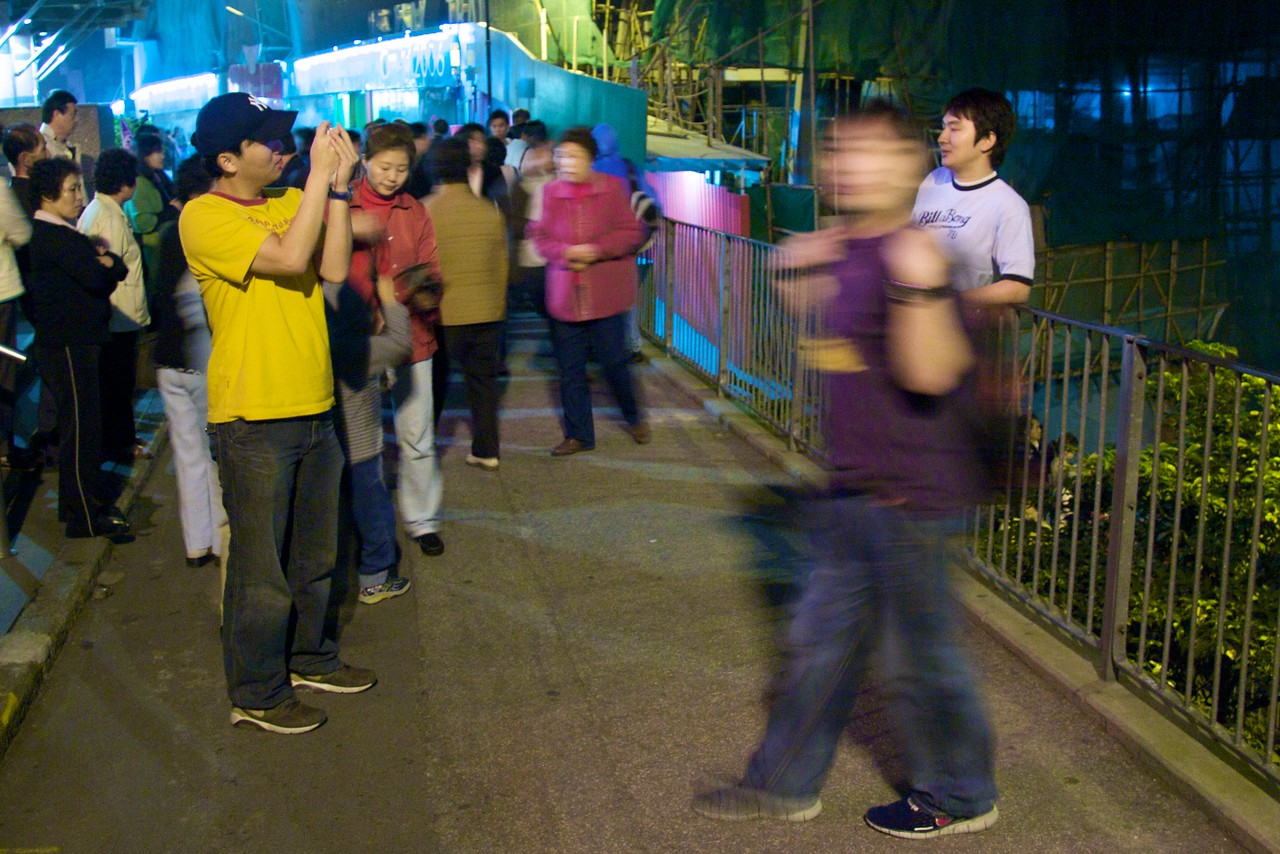 Posing • When I went back to The Peak at night, there were even more people there than earlier in the day—here they were lining up to have their photos taken in front of the impressive Hong Kong skyline.