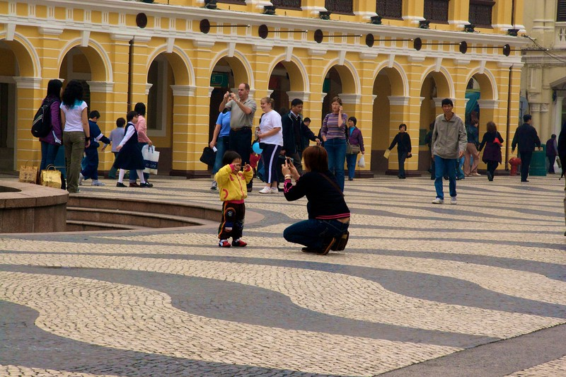 Largo do Senado • A woman takes a photo of her young son in the Largo do Senado in Macau.   The largo had a distinctly 'European' feel bestowed on it by the Portuguese, particularly in the tiling on the ground and the colonnade finished with yellow-painted stucco.