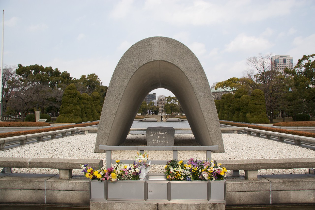 Memorial Cenotaph, Hiroshima • The shape of the Memorial Cenotaph in the Peace Park in Hiroshima is instantly recognisable. There is a service commemorating the bombing of Hiroshima every August, on the anniversary of the bombing. There is a 'coffin' underneath the concrete arch which contains the names of those identified as having been killed by the blast.<br /> <br /> Through the arch you can see the 'atomic bomb dome', which was originally the Hiroshima Prefectural Industrial Promotion Hall. It has been maintained in the state in which it was left following the bombing as a memorial. When I was there it was shrouded in scaffolding: the city has only recently arranged for the structure to be assessed annually.