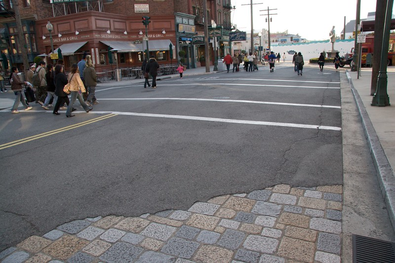 Cracked streets • At first when I was wandering around the 'streets' of the theme park Universal Studios Japan, I thought that it was curious how run down they appeared. Then it occurred to me that people don't really build streets with tarmac on top of stone paving in this way any more.   This was all part of the specialised 'ageing' process employed by Hollywood set dressers which helps to increase the credibility of exterior sets.