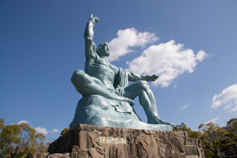 Peace statue • The enormous Peace Statue in the Peace Park at Nagasaki. The statue's right hand is pointing to the sky to warn of the provenance of the bomb, and the left hand is extended to ward off the forces of evil.