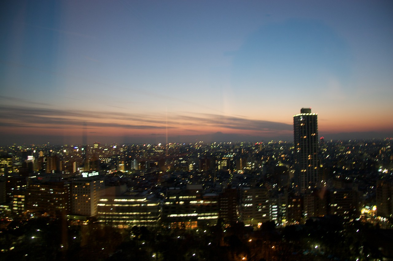 Tokyo at sunset • Like the dunce that I am, I failed to turn off the light in my room which is why you can see the reflection of the window in this photo.