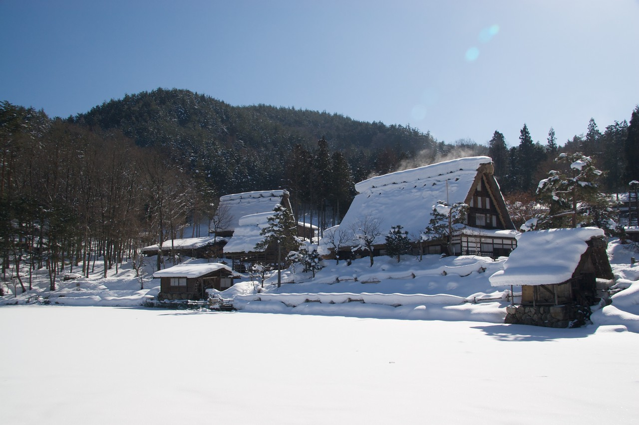 Hida Folk Village • A collection of antique traditional Japanese houses and farm-buildings have been transferred to this 'village', on a mountain just over a mile from Takayama.<br /> <br /> The large flat area covered in snow is in warmer times a lake: it had frozen over and been covered with snow.