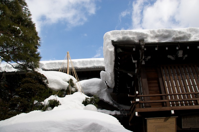 Takayama roofs • Many roofs in the town had a heavy layer of snow covering them—I didn't wonder that elsewhere in the country this season roofs have caved in. Some people were actively shovelling snow from their roofs while I was there. This was nothing compared to what I would see the following day on the roofs of the preserved traditional houses at Hida Folk Village.