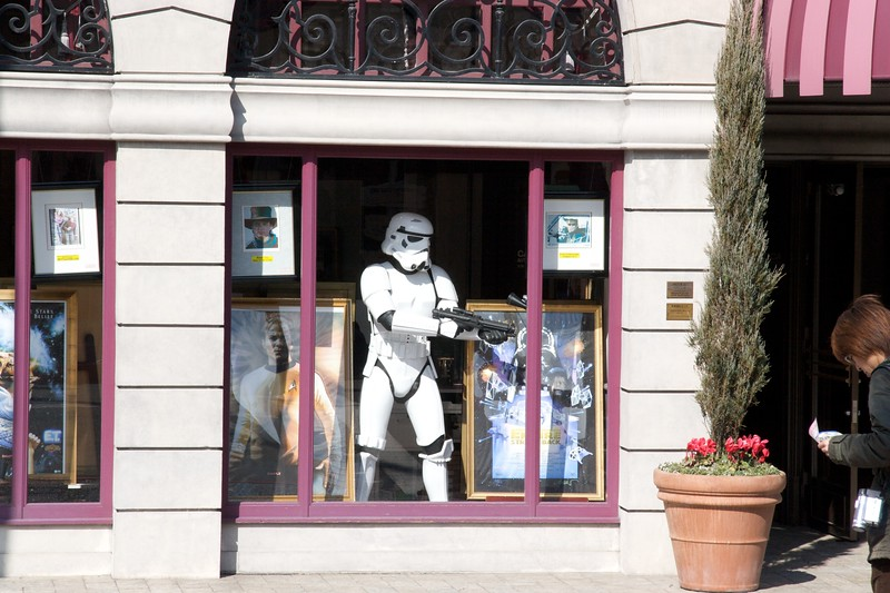 Stormtrooper • A stormtrooper's costume from the <cite>Star Wars</cite> series stands, with a blaster, in the window of a shop which sold various autographed posters. I don't think the storm trooper was for sale: if he had been, judging by the price of a few of the posters in the shop, then that would have been one expensive lump of plastic. <cite>Star Wars</cite> is of course not a Universal Pictures film—it was distributed by 20th Century Fox—but I think this shop was independent of the management of the Universal Studios Japan theme park.