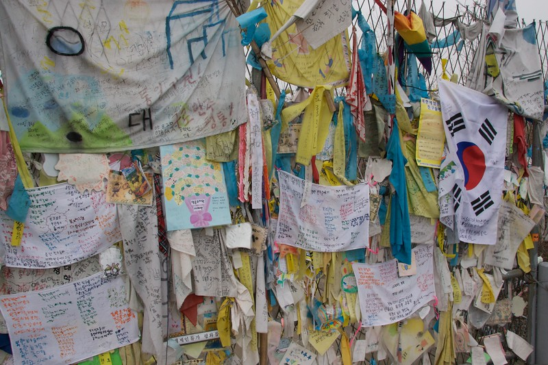 "Messages • The fence across the 'Freedom Bridge' (now blocked up) which links the two Koreas across the <abbr title=""De-militarized Zone"">DMZ</abbr> and military demarcation line is covered with expressions of desire for reunification."