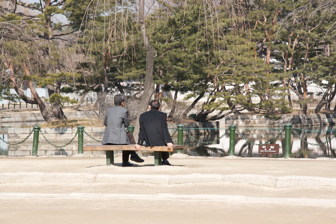 Men • Two men sit next to the body of water in the middle of which sits Gyeonghoeru, the banquet-house of the Seoul imperial palace, Gyeongbokgung.