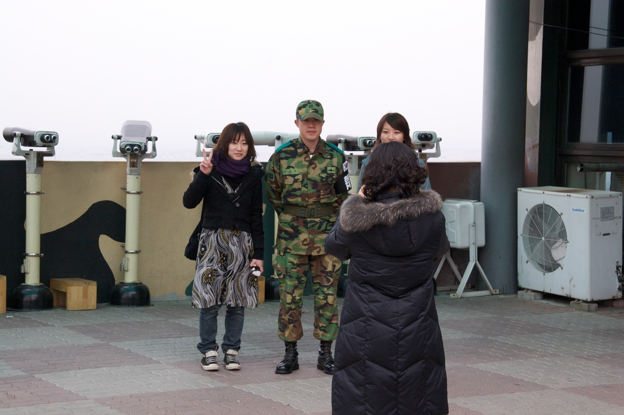 Photocall • A couple of Japanese tourists from my tour group have their photo taken with a Korean soldier at Dora observatory.
