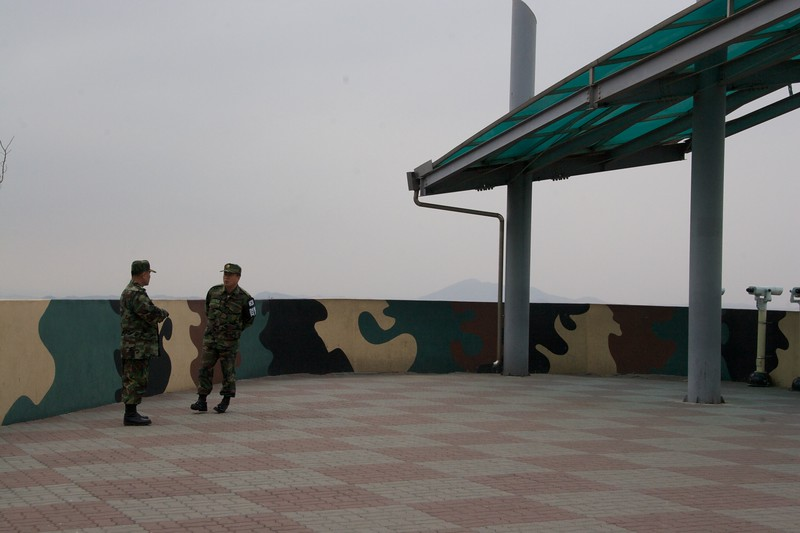 "Chatting • A couple of Korean soldiers stand chatting at Dora observatory, which overlooks the <abbr title=""De-Militarized Zone"">DMZ</abbr> and over North Korea."