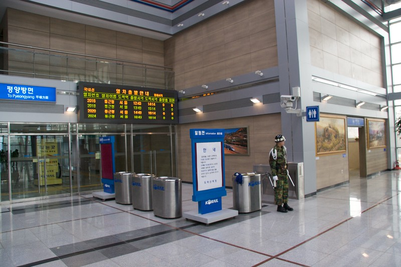 Standing guard • A Korean soldier stands guard at Dorasan railway station. The electronic display board behind him reveals that all trains from this station are going only to Seoul, 56km south.