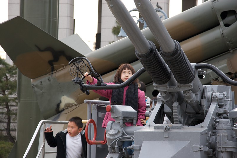 Watch out, Kims • Children climbing on an anti-aircraft gun, part of the display of military hardware outside the War Memorial Museum in Seoul.